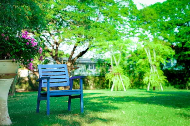 Une chaise bleue en bois seule dans le jardin. se sentir seul, mais relaxant et retraite