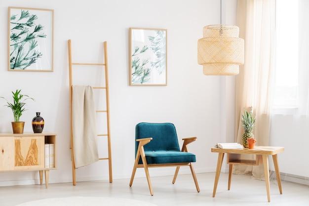 Chaise bleue dans le salon avec ananas sur table en bois et vase décoratif sur placard rustique