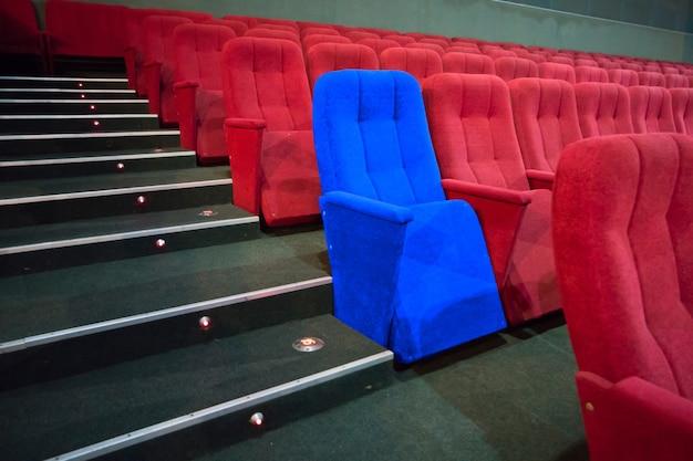 Chaise bleue entre des rangées de sièges rouges dans le théâtre moderne. scène de cinéma concept