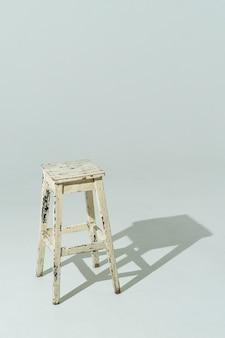 Chaise en bois authentique avec une vieille peinture de couleur laitière. meubles blancs sur mur léger
