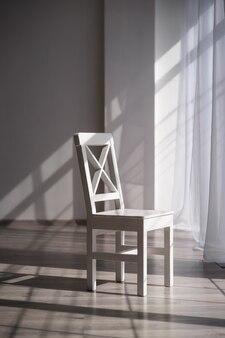 Chaise en bois blanc dans le contexte d'une belle chambre spacieuse et lumineuse avec des murs blancs et du parquet clair au soleil du matin
