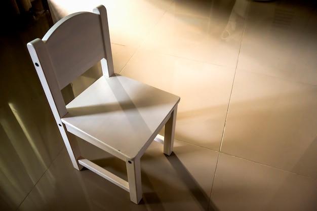 Chaise en bois blanc à la lumière de la porte