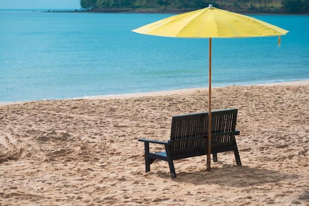 Chaise en bois avec parasol jaune sur la plage