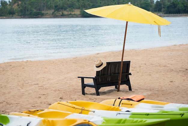 Chaise en bois avec parasol jaune sur la plage.