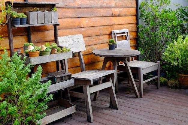 Chaise en bois et table ou canapé en bois avec des arbres à côté du mur en bois dans un style rétro