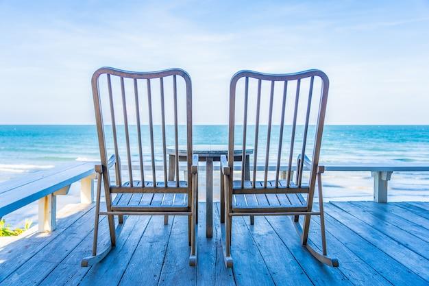 Chaise en bois vide et table au patio extérieur avec belle plage tropicale et la mer