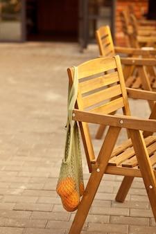 Chaise de café en rotin avec sac en filet avec fruits oranges. café de la rue.