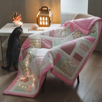 Chaise confortable avec des aiguilles à tricoter pour couverture et un chat rigolo