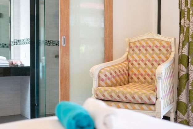 Chaise en cuir, table, fleur et lampe près du lit dans la chambre de la maison ou à la maison