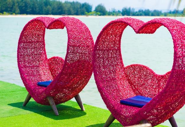 Chaise en forme de coeur rose sur la plage.