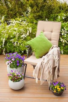Chaise de jardin sur terrasse, fleurs de pensée