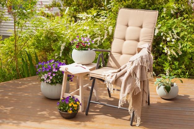 Chaise de jardin sur terrasse et fleurs de pensée