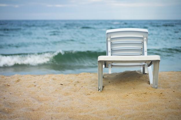 Chaise longue blanche en plastique sur la plage déserte