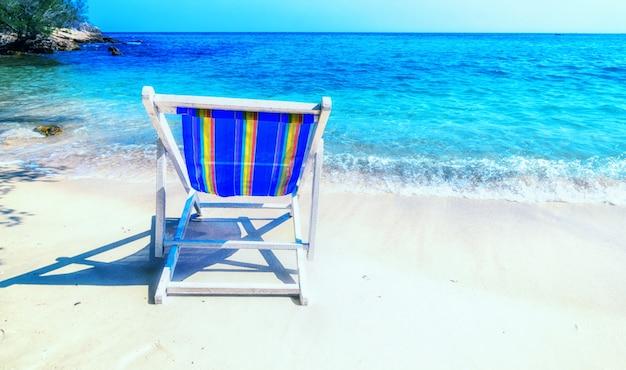Chaise longue lumineuse sur le sable au bord de la mer.
