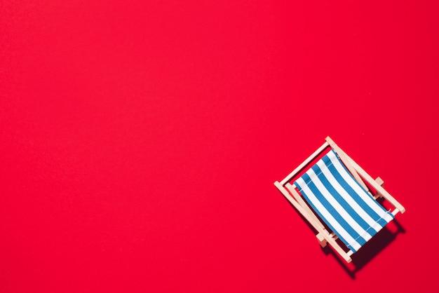 Chaise longue avec des ombres dures sur fond de papier rouge.
