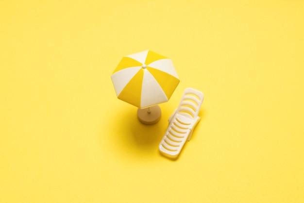 Chaise longue et parasol jaune sur fond jaune.