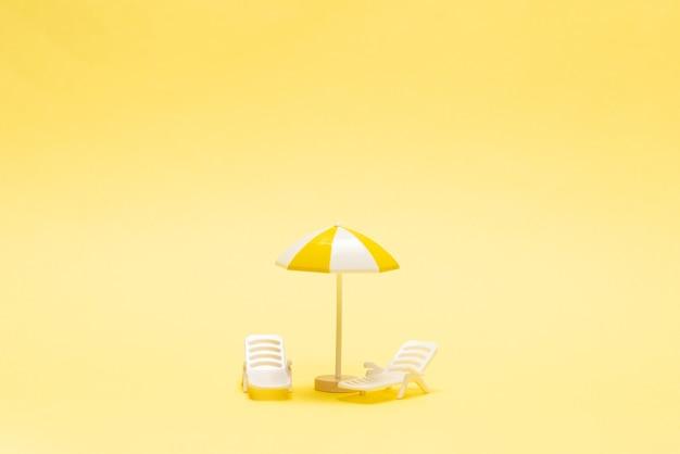 Chaise longue et parasol jaune sur une surface jaune.