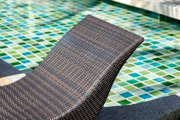 Chaise longue en rotin près de la piscine dans un hôtel tropical, gros plan, thaïlande