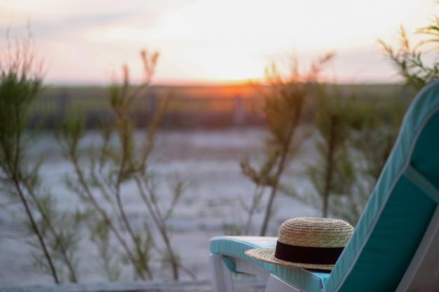 Chaise longue sur le sable blanc avec un chapeau d'été plage avec une chaise longue au lever du soleil plage avec un soleil
