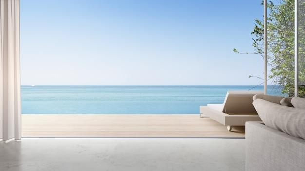 Chaise longue sur terrasse près d'un salon lumineux et canapé dans une maison de plage moderne