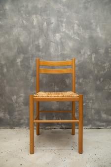 Chaise en osier sur mur de béton gris à l'intérieur, espace vide, espace de copie pour le texte. élément intérieur, mobilier
