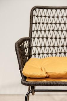 Chaise en osier noir avec détails d'oreillers jaunes