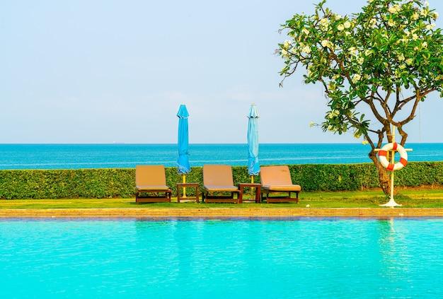 Chaise piscine ou lit piscine et parasol autour de la piscine avec fond de mer - concept de vacances et de vacances
