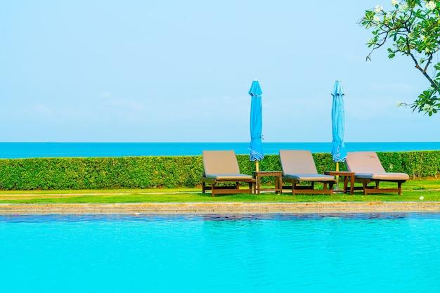 Chaise de piscine ou lit de piscine et parasol autour de la piscine avec mer. concept de vacances et de vacances