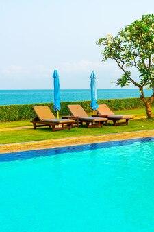 Chaise de piscine ou lit de piscine et parasol autour de la piscine avec mer
