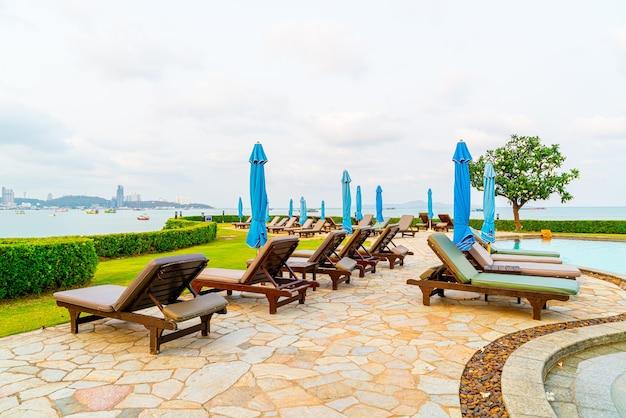 Chaise piscine ou lit piscine et parasol autour de la piscine avec plage de la mer à pattaya en thaïlande
