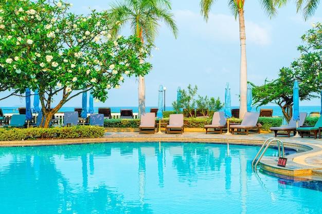 Chaise piscine et parasol autour de la piscine avec cocotier - concept vacances et vacances