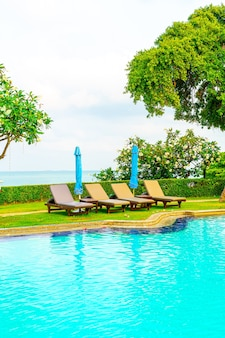 Chaise piscine et parasol autour de la piscine avec fond de mer océan