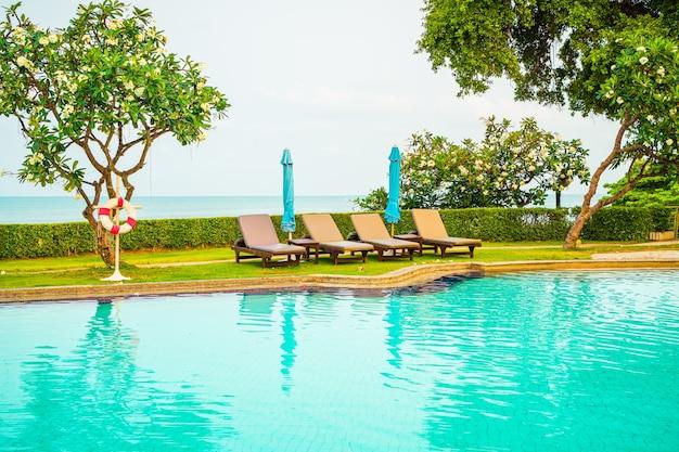 Chaise de piscine avec parasol autour de la piscine