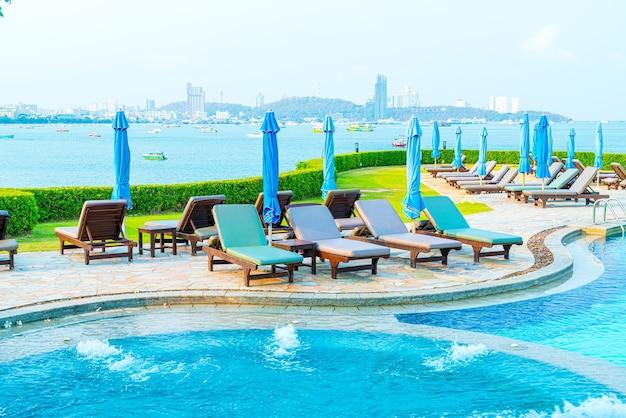 Chaise de piscine et parasol autour de la piscine