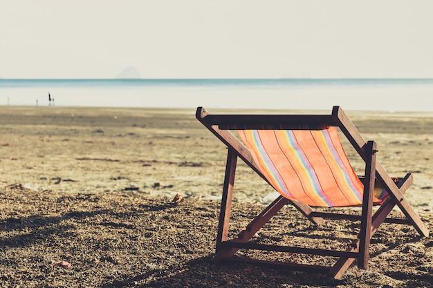 Une chaise de plage avec la lumière du coucher du soleil lumière été unique voyage concept de vacances couleur ton unique