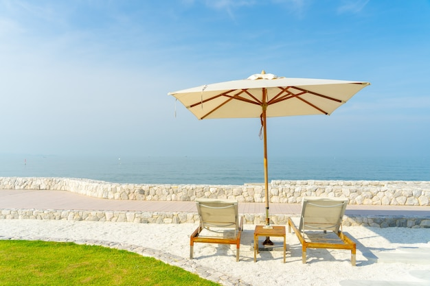Chaise de plage et parasol avec beau ciel bleu