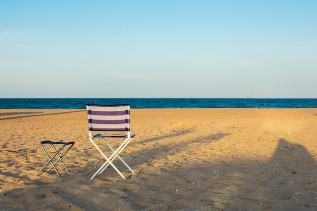 Une chaise de plage sur une plage déserte au coucher du soleil.