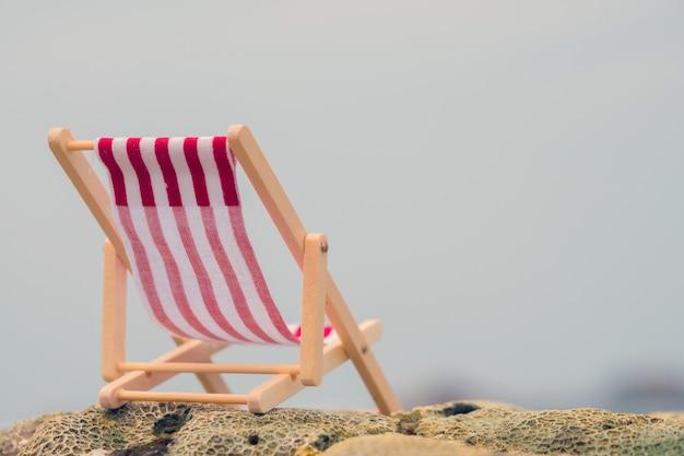 Chaise de plage rouge rayée.