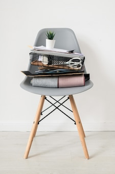 Chaise en plastique gris avec pile de fournitures de bureau ou de trucs de concepteur d'intérieur avec petit pot de fleurs sur son haut debout dans l'isolement par un mur blanc