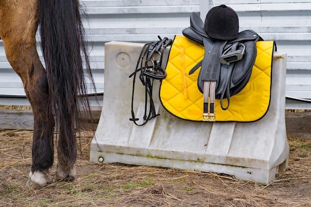 Chaise pour monter à cheval, casque de protection et autre équitation. préparation du cheval des cavaliers de compétition
