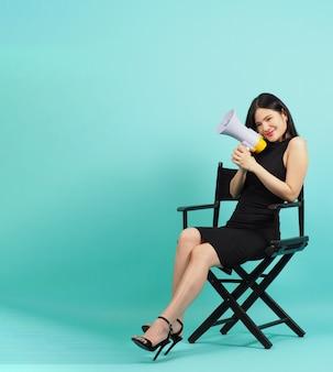 Chaise de réalisateur noire, femme asiatique, tient un mégaphone et s'assoit sur une chaise, fond de menthe