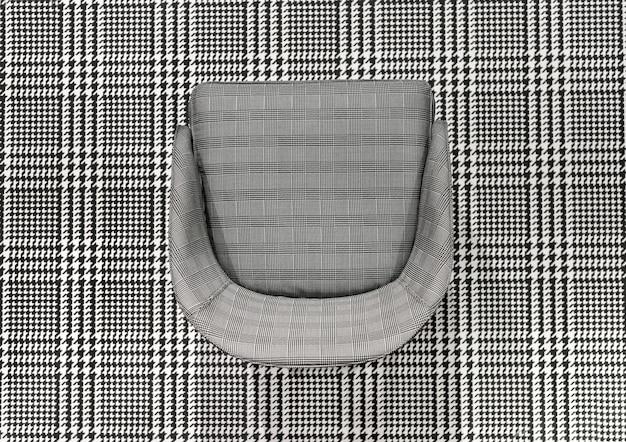 Chaise rembourrée à carreaux juxtaposée à un textile à carreaux tissé noir et blanc assorti dans une vue de haut en bas pour un effet de contraste élevé pour le design