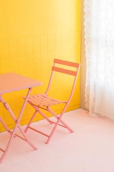 Chaise rose vide et table avec mur jaune