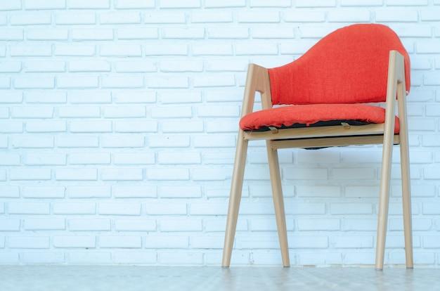 Chaise rouge sur fond de briques blanches, salle moderne, espace copie.