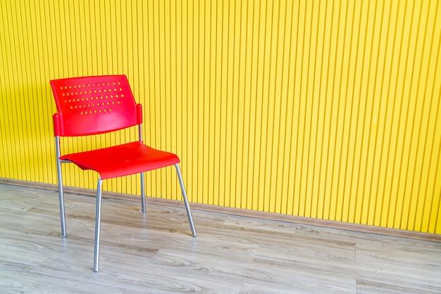 Chaise rouge avec mur jaune