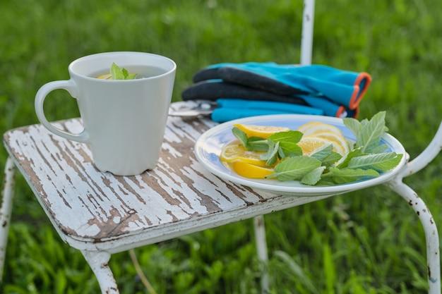 Chaise avec sécateur de jardin, gants, tasse de thé à la menthe fraîche avec du citron