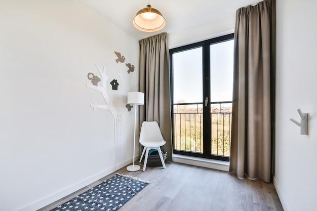 Chaise de style minimaliste et lampe placée près de la fenêtre avec rideaux et décoration d'arbre de dessin animé dans le coin de la chambre d'enfant
