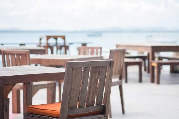 Chaise et table de café-restaurant sur le pont du balcon à l'océan bleu de bord de mer.