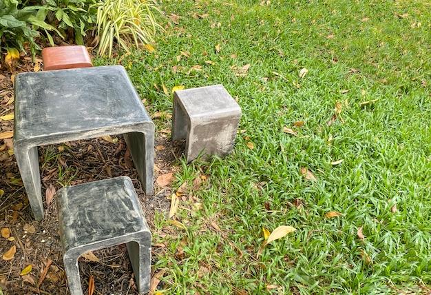 Chaise et table en pierre au parc extérieur vert.