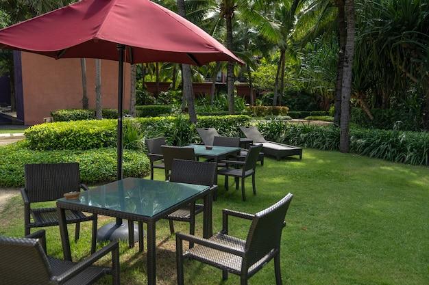 La chaise de vannerie, la table et le parasol rouge posés dans le jardin, dans l'espace détente.